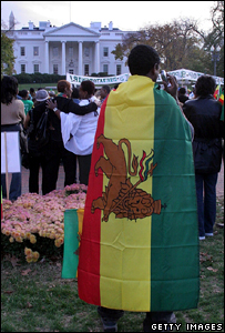 A demonstrator stands draped with the red, yellow and green flag of Ethiopia