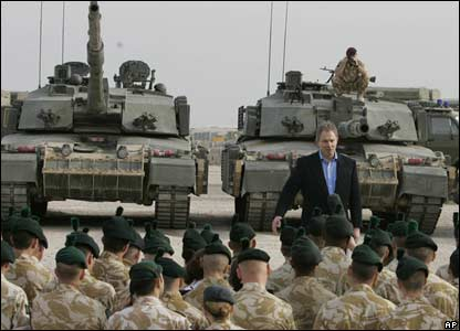 Tony Blair standing in front of tanks