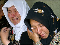 Uzbek women cry in temporary refugee camp on border with Kyrgyzstan