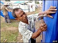 A man builds temporary toilets on a camp for tsunami victims in Banda Aceh, Sumatra, on 2 December