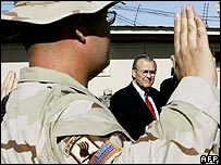 Donald Rumsfeld watches as an Army specialist takes an oath as part of re-enlistment