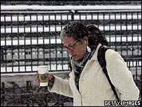 Woman using an iPod while struggling through snowy weather