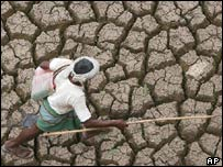 A farmer walking over dry earth