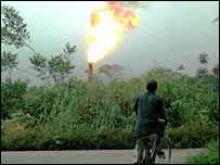 Man watches gas flare.  Image: Friends of the Earth International