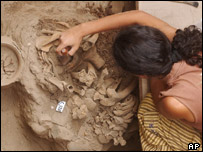 An unidentified archaeologist cleans a group of remains uncovered in the sanctuary of in Pachacamac, Peru