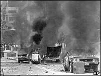 Cars burn on the streets of Kwangju, South Korea on 19 May 1980, as anti-government demonstrators protest in the background
