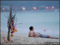 Man relaxing next to flowers and candles at Patong Beach, Thailand