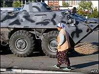A local resident walks past a tank at the centre of the Uzbek town of Andijan, 17 May 2005