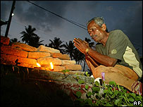 A man prays for the wife he lost to the tsunami at Peraliya, Sri Lanka