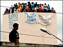 Inmates of the Urso Branco prison sit on one of the facility's water towers as a policeman looks on