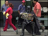 Fan dressed as Darth Vader reading a newspaper in Lima, Peru
