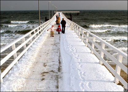 Tourists walk on the snowy pier in the German Baltic Sea resort of Timmendorfer Strand