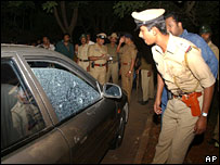 A police officer in Bangalore stands by a car damaged by gunfire