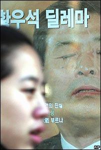 Persona camina frente a un afiche con foto de Hwang Woo-suk