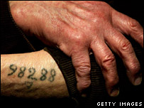 Auschwitz survivor Leon Greenman shows his prison number tattooed on his arm