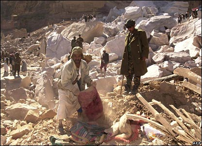 Yemenis gather on the rubble of their houses following an overnight landslide