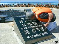 Tokyo Gov. Shintaro Ishihara kisses the plate that declares 'Okinotorishima, Japan' in Japanese after landing on Higashi Kojima, one of the two Okinotorishima islets, May 20, 2005.