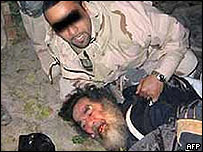US soldier taking Saddam Hussein from his hiding place in ad-Dawr, 13 December, 2003