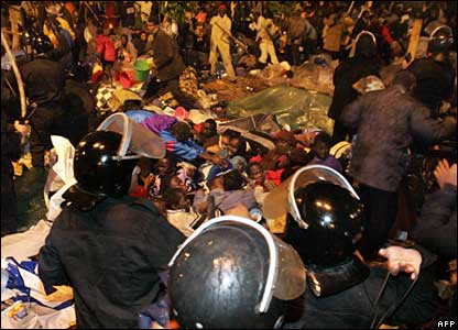 Police surround Sudanese sitting on the ground