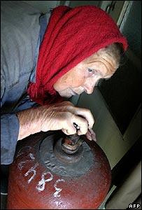 Ukrainian villager closes a valve on a gas cylinder