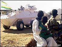 Children watch as three Canadian APCs arrive for the African Union mission in Darfur