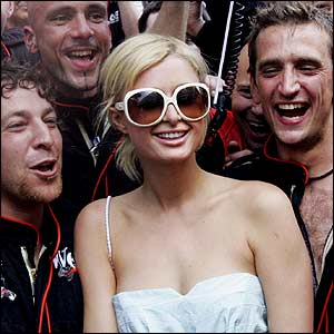 The McLaren pit crew celebrate with Paris Hilton
