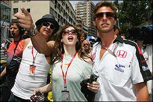 Musician Kid Rock and friend are escorted through the pre-race crowd by Jenson Button