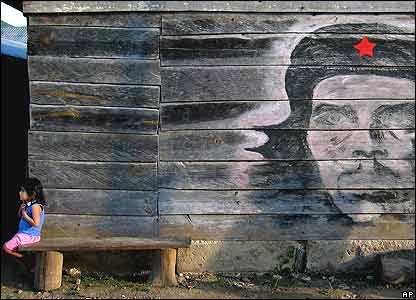 Girl sits next to a mural of Che Guevara in La Garrucha