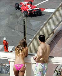 Onlookers watch the progress of a Ferrari car