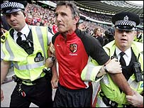 Guy Noves is led off the Murrayfield pitch by police