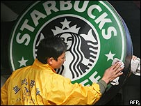 Starbucks worker cleans window of a store in Beijing