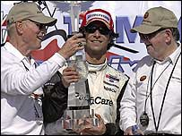 Bruno Junqueira (c) celebrates with team owners Paul Newman (l) and Carl Haas