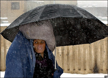 An Afghan woman walks through snowy weather with a sack of food on her head after picking it up from Care International at a distribution centre in Kabul