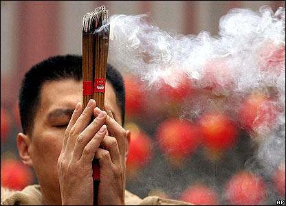 A Chinese Buddhist burns joss sticks to welcome in the new year at Yufo Temple in Shanghai