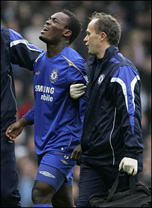 Chelsea's Michael Essien leaves the field injured