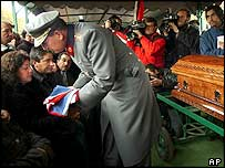 Chilean general presents relative of a dead soldier with a Chilean flag