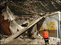Rescue worker looks at collapsed roof