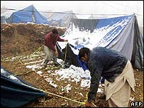 Earthquake survivors clear their tents of snow near Muzaffarabad in Pakistani Kashmir