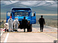 Medical workers sanitise a truck in north-western China