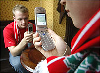 Football fans using their mobile phones