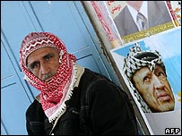 Man sits beside poster of the late Yasser Arafat in Ramallah