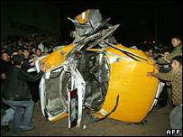 Palestinian onlookers gather around the car following the air strike in Jabaliya