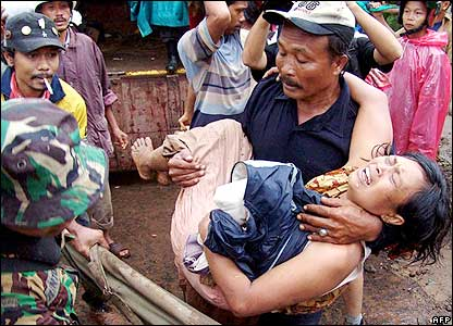 Indonesian residents and soldiers rescue a young girl from a village in Jember, 03 January 2006.