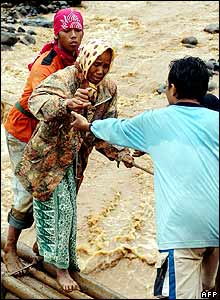 Indonesian search and rescue members help an elderly woman during an evacuation at a village in Jember, 03 January 2006.