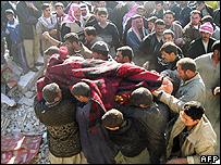 Corpse being carried from the collapsed house in Baiji