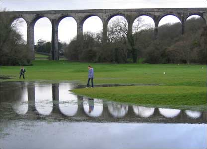 Martin Cooper's niece and nephew Cerian and Gareth Pardoe on the flooded pitch and putt golf course in front of the the railway bridge in Porthkerry, in the Vale of Glamorgan