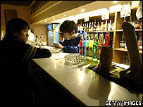 A bartender and a patron on a quiet night at a Beijing gay bar, 10/02/2004