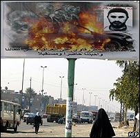A woman walks under a huge anti-terror advertisement showing the image of fire and the portrait of Abu Musab al-Zarqawi