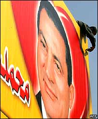 A campaign worker in Cairo adds the finishing touches to a billboard with the image of Egyptian President Hosni Mubarak.