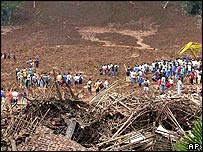 Rescuers and people from neighbouring villages stand in the wreckage of Sijeruk village in Banjarnegara district, Central Java, Indonesia Wednesday Jan. 4, 2006.